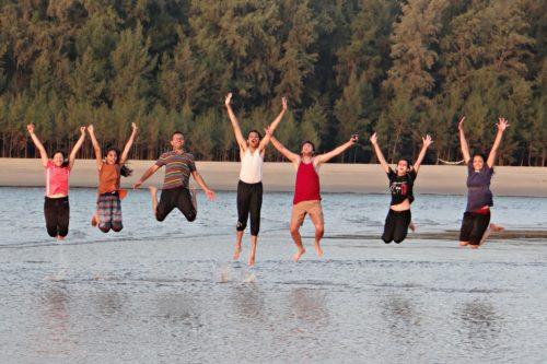 grupo de jóvenes saltando en la playa